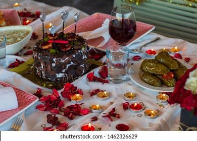 Birthday table. Cake, wine, roses, candes and traditional Turkish foods on the celebration table.