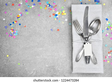 Birthday table setting background with copy space. Concrete background with napkin, silverware and name tag. Cutlery with fork, knife and spoon. Top view, party or event decoration with confetti.