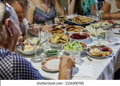 Birthday, Thanksgiving, Christmas, New Year, festive dinner, a table, big family at big table eating verious food together. gathering or celebration concept, close up