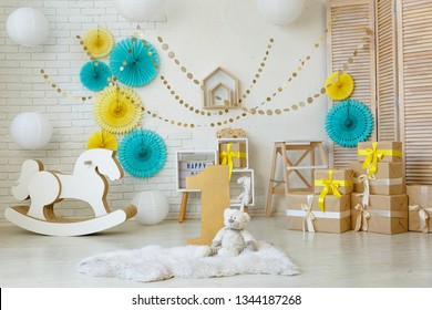 Birthday tiffany and yellow decorations with gifts, toys, garlands and figure for little baby party on a white bricks background.