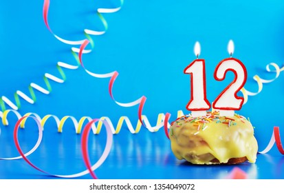 Birthday of twelve years. Cupcake with white burning candle in the form of number 12. Vivid blue background with copy space