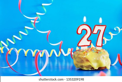 Birthday of twenty seven years. Cupcake with white burning candle in the form of number 27. Vivid blue background with copy space
