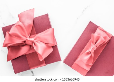 Birthday, wedding and girly branding concept - Coral gift box with silk bow on marble background, girl baby shower present and glamour fashion gift for luxury beauty brand, holiday flatlay art design