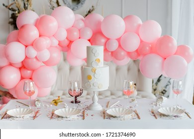 Birthday or wedding table setting in white colors with cocktails in glasses. Baby shower or girl party. Selective focus. Balloon garland
