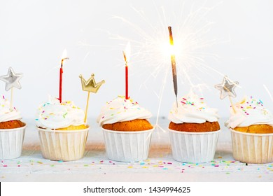 Birthday white cupcakes decorated with burning candles and firework, festive composition