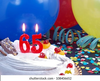 Birthday-anniversary cake with red candles showing Nr. 65