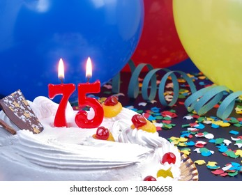 Birthday-anniversary cake with red candles showing Nr. 75