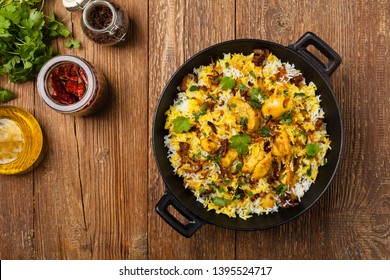 Biryani with chicken. Traditional Indian dish of rice and chicken marinated in spices and yoghurt.Top view. natural wooden background.