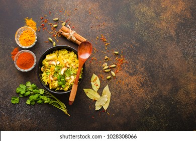 Biryani rice, traditional Indian dish. Biryani spicy rice, chicken, nuts. Indian rice bowl, spices, herbs, rustic stone background. Top view. Space for text. Asian style biryani rice. Indian dinner