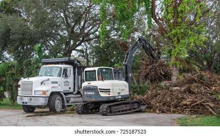 BISCAYNE PARK, FL - September 25th, 2017: Trucks and excavator clean derbies piles after hurricane Irma in Miami