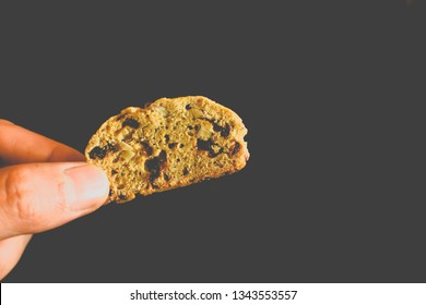 Close​ up​ of​ Hand​ holding​ baked​ cranberry​ and peanut​ biscotti on​ black background.​ Texture​ of​ traditional​ biscotti close​ up​ and​ copy​ space​ for text.​ Homemade bekery​ concept.