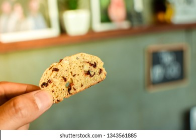 Hand​ holding​ homemade​ baked​ cranberry​ and almond​ biscotti on​ blurry background.​ Texture​ of​ traditional​ biscotti close​ up​ and​ copy​ space​ for text.​ Homemade bekery​ concept.