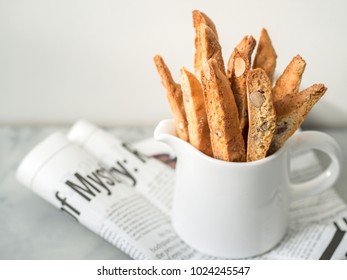 Biscotti (cantuccini) - traditional Italian almond dessert in a white cup close-up, against the background of the newspaper.
