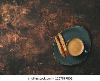 Biscotti cookies with almonds and one cup of coffee espresso on dark copper background with copy space. Flat lay.