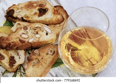 Biscotti cookies with sweet wine Vin Santo on wooden desk. Cup of wine, sweet wine and dessert biscotti.  Dry Cantucci with alcohol on table.