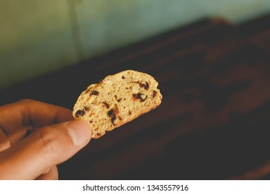 Hand​ holding​ baked​ cranberry​ and peanut​ biscotti on​ blurry​ wooden​ background.​ Traditional​ biscotti close​ up​ and​ copy​ space​ for text.​ Homemade bekery​ concept.