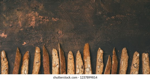 Biscotti - Traditional Italian Almond Dessert On Dark Copper Background. Cookies Arranged On The Bottom Of Third Of The Frame Horizontal Composition With Copy Space. Top View, Selective Focus.