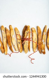 Biscotti-traditional Italian almond dessert tied with a rope of three pieces on a light surface with a copy space for the text, vertical composition.