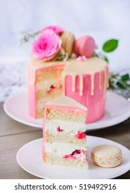 Biscuit cake with buttercream and raspberries inside, pink frosting and white chocolate ganache. Decorated with flowers and macaroons