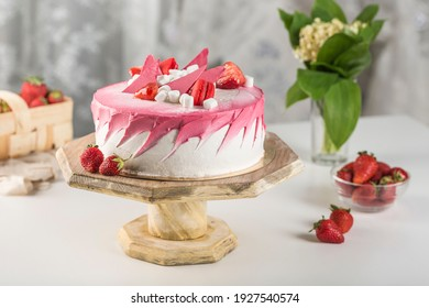 Biscuit cake with strawberry filling and fresh strawberries on a wooden stand on a light background. Side view with a copy space for the text. A delicious dessert for a holiday and birthday.