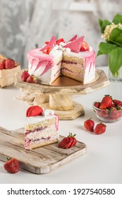 Biscuit cake with strawberry filling and fresh strawberries with a cut piece on a wooden stand on a light background. Side view with a copy space for the text. Dessert for a holiday and birthday.