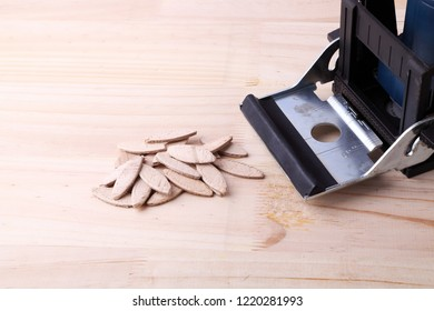 Biscuit joiner on wood with a group of biscuits