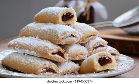 Biscuit rolls filled with jam with powdered sugar on top on plate over wooden table