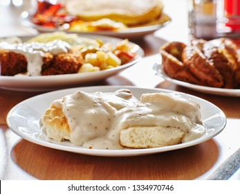 biscuits and gravy with breakfast foods on plate