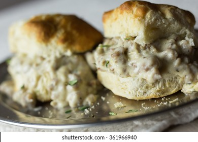 Biscuits and gravy on a metallic tray.