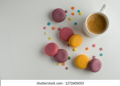 Biscuits macaron or macaroon on white background, colorful almond cookies with a cup of coffee, top view.