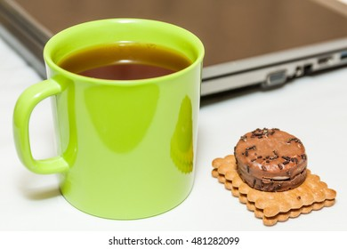Biscuits and tea in green cup with laptop as background
