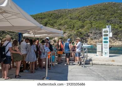 Bisevo, Croatia - Aug 16, 2020: Tourist queue to board on boat to blue cave tour in Komiza
