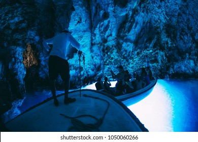 BISEVO, CROATIA - AUGUST 22, 2017. - Croatian wonder. Tourist visiting the inside of the Blue cave, Bisevo island, Croatia. Pictures taken in complete darkness.