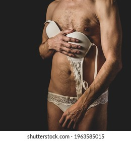 Bisexual young man in white lace women's lingerie on dark background