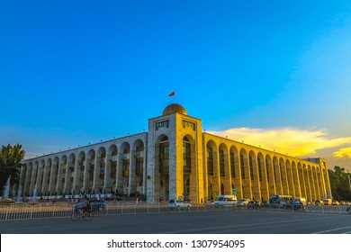 Bishkek Ala Too Square Commercial Building with Kyrgyzstan Waving Flag and Busy Road Traffic