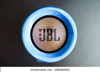 Bishkek, Kyrgyzstan - 24 February, 2018: Blue Wet JBL Charge 3 logo of Wireless Portable Bluetooth Stereo Speaker . Flat lay top view. Some water drops in logo. IPX7 Waterproof Rating