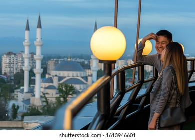 Bishkek, Kyrgyzstan - April 29, 2018: a guy smiling with a girl with on the backgroun the Bishkek Central Mosque, formerly Borborduk Mosque