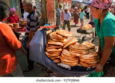 BISHKEK, KYRGYZSTAN - AUG 1: Women selling traditional Central Asian bread on the popular Osh market on August 1, 2013. In Kyrgyzstan 34 perc. are under age of 15 and 6.2 perc. are over 65.