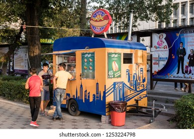 Bishkek, Kyrgyzstan August 18 2018: Booth in the pedestrian area of Bishkek selling hot dogs. Three people are waiting for the preparation of their hot dog