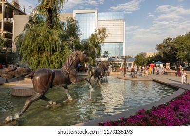 Bishkek, Kyrgyzstan August 9 2018: Pedestrian area with fountain in the center of Bishkek during the sunset