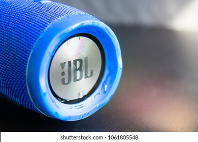 Bishkek, Kyrgyzstan - February 24, 2018: JBL logo on a blue bluetooth speaker with textile and metalic texture