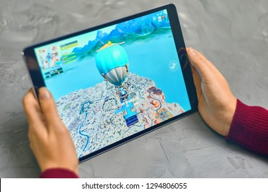 Bishkek, Kyrgyzstan - January 21, 2019: Woman playing fortnite game of epic games company on Apple ios tablet iPad Pro. Gameplay Action
