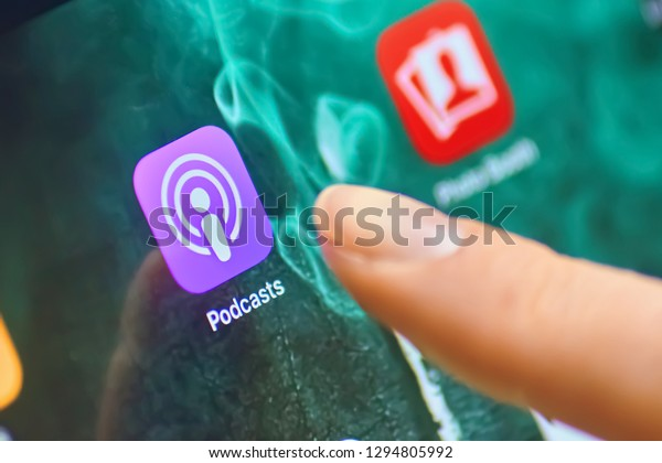 Bishkek, Kyrgyzstan - January 21, 2019: Close up to Apple Podcasts app on the screen of an Ipad Pro with personalized background and female finger touch on the app