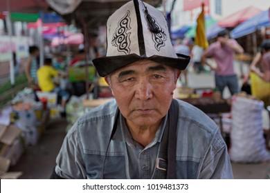 BISHKEK, KYRGYZSTAN - MAY 27, 2017: Kyrgyz man in Osh Bazaar wears local hat and looks at me, in Bishkek, Kyrgyzstan.