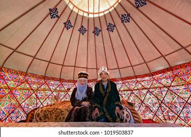 BISHKEK, KYRGYZSTAN - MAY 27, 2017: Kyrgyz couple in national costumes, in a nomadic tent known as yurt, near the city of Bishkek, Kyrgyzstan.