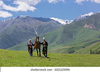 BISHKEK, KYRGYZSTAN - MAY 27, 2017: Nomadic couple and their horse in the mountains near Bishkek, Kyrgyzstan.