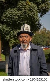 Bishkek, Kyrgyzstan - September 19, 2018 :  Man in traditional Kyrgyz hat in park in Bishkek, Kyrgyzstan.