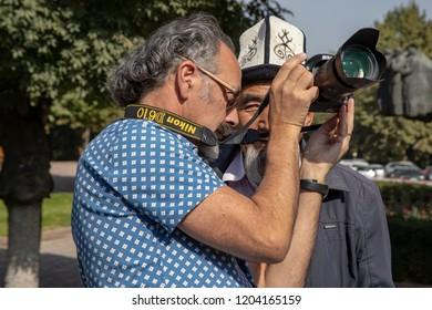 Bishkek, Kyrgyzstan - September 19, 2018 :  American tourists sharing portrait of man in traditional Kyrgyz hat in park in Bishkek, Kyrgyzstan.