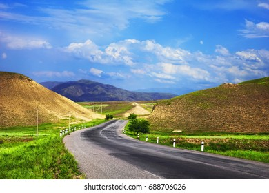 Bishkek - Osh highway. Awesome scenic view - twisty road across the green field between barren yellow mountains at the background of dramatic cloudy sky, Tien Shan range, Kyrgyzstan, Central Asia