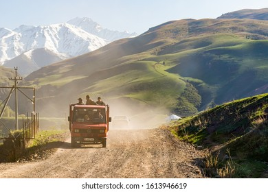 Bishkek province, Kyrgyzstan - April 28, 2018: men on a truck on motorbikes on a dusty gravel road in the kyrgyz countryside, with mountains covered with snow